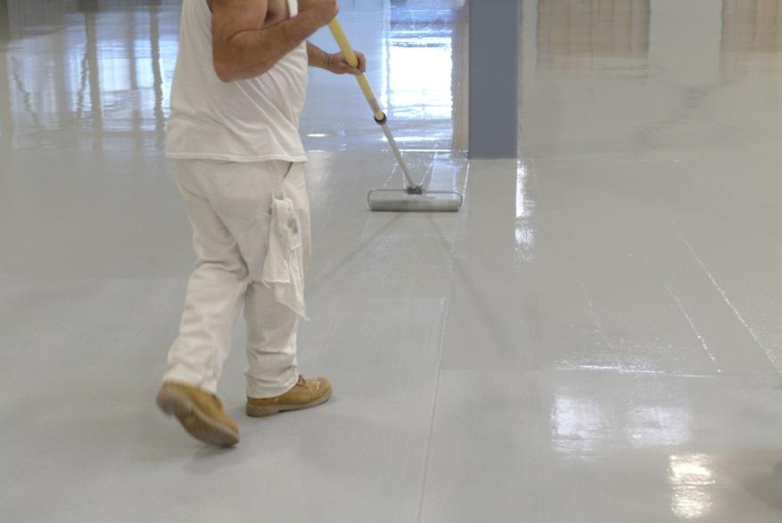 Worker Applying Epoxy Floor Coating | Floorguard.com